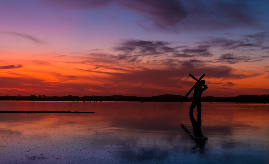Man carrying a cross on a lake, with a fire like sunset in the sky.